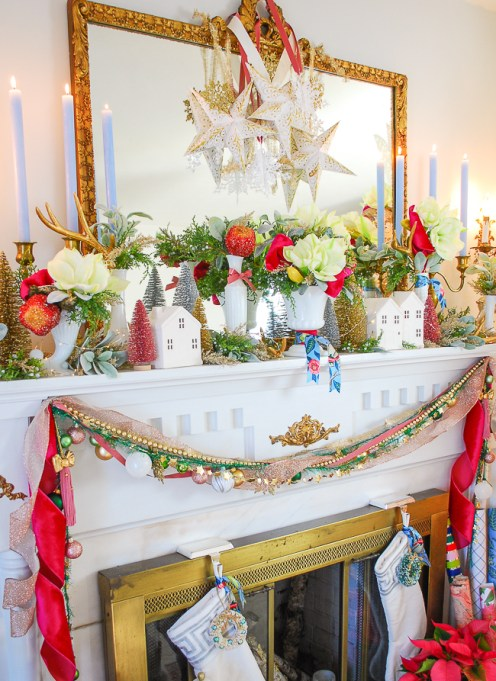 White amaryllis, hot pink ribbon, and greenery mixed with a white Christmas village make for a colorful and whimsical holiday mantel