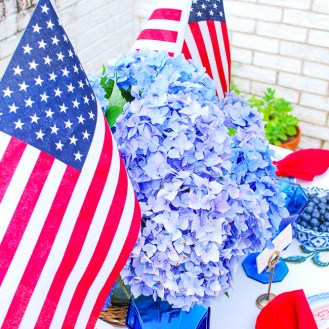 Vibrant blue hydrangea July 4th centerpiece with US flags
