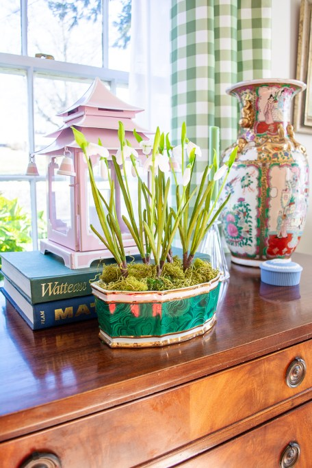 Malachite planter with snowdrops on traditional sideboard - classic green accessory