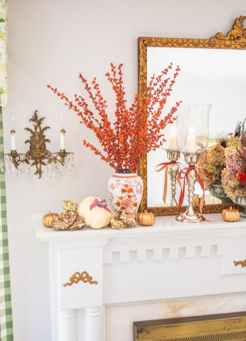 Branches of orange berries fill a Chinese orange and white vase surrounded by white pumpkins and preserved hydrangea blooms