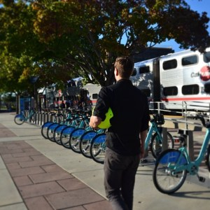 From Bay Area Bike Share's Instagram feed. A man walks near the Redwood City Caltrain Station and bike share station.