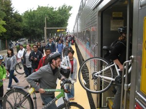Cyclists load their bikes into Caltrain's bike car.