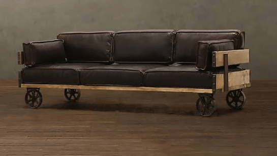 a dark brown couch on wheels sits in an empty beige room with dark wood floors.