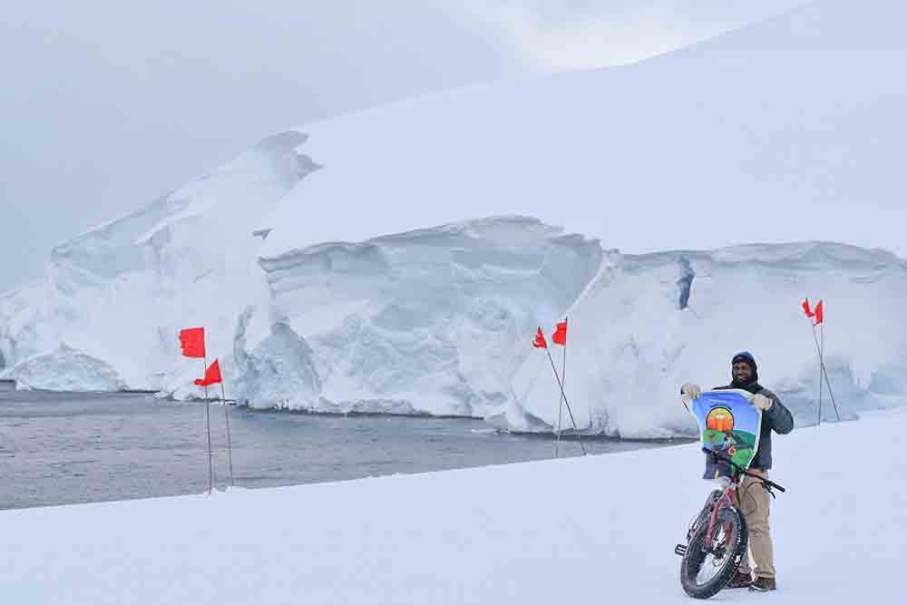Sridhar Anandakrishnan in Antarctica holding Pedals and Pints Jersey