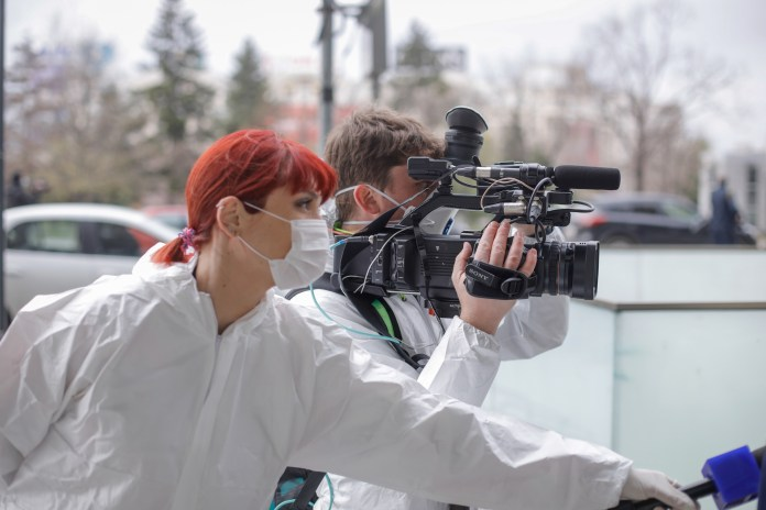 A reporter and a cameraman wear protective clothing and masks while reporting on the coronavirus from the field.