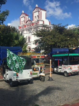 Tuktuks, church and a public square - Guatapé