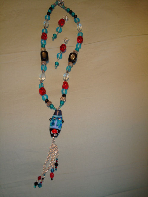Handblown glass face with multi colored stones and silver dangles