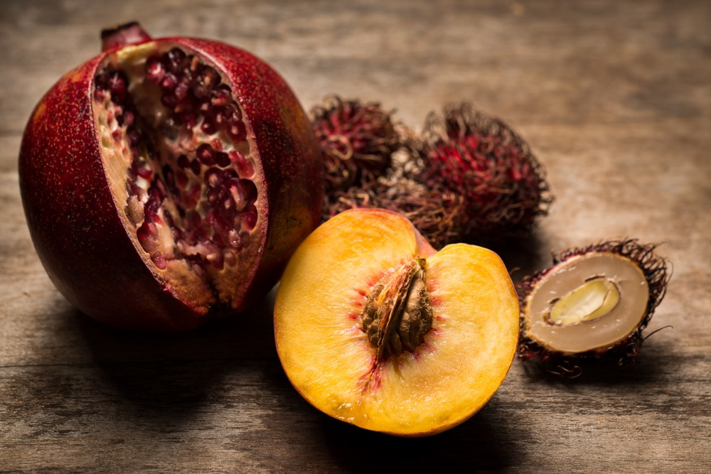 Pomegranate & peach on a wood background