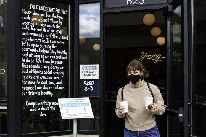 woman grabbing coffee with mask