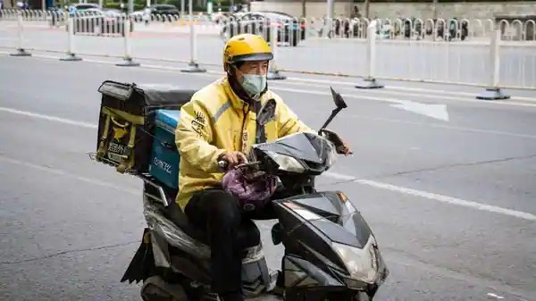 A food delivery courier for Meituan rides a motorcycle in Beijing, China. (Bloomberg)