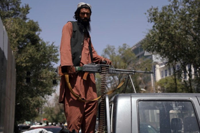 A Taliban fighter sits on the back of vehicle with a machine gun in front of the main gate leading to the Afghan presidential palace, in Kabul, on Aug. 16, 2021.