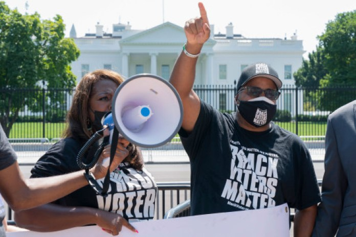 LaTosha Brown (left) and Cliff Albright rally for voting rights near the White House in Washington, DC on August 24, 2021.