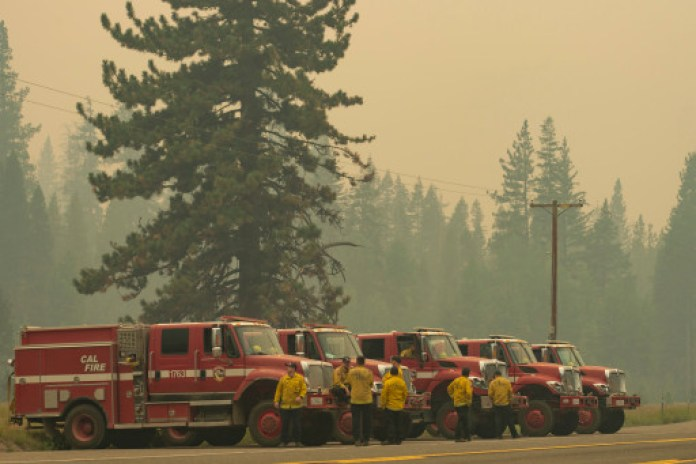 Cal Fire vehicles line up along Highway 50 in Strawberry, California, in preparation for the Caldor Fire to reach Lake Tahoe.