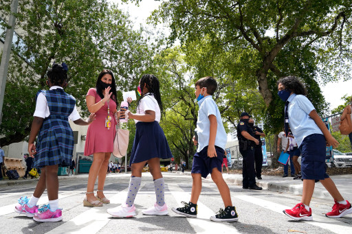Teacher Vanessa Rosario greets students outside of iPrep Academy on the first day of school, Monday, Aug. 23, 2021, in Miami.