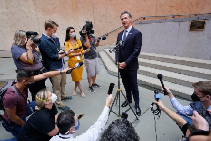 California Gov. Gavin Newsom responds to a question while meeting with reporters after casting his recall ballot.