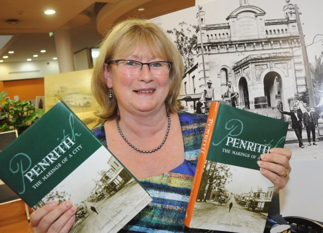 Lorraine Stackker holding a copy of her latest book, Penrith:The Makings of a City