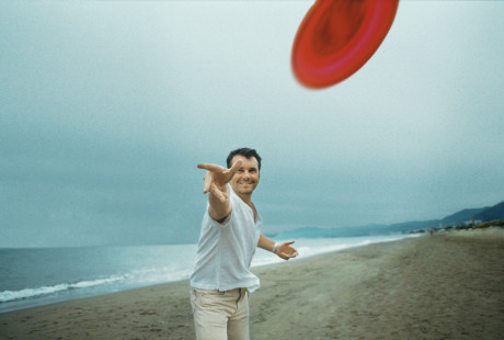 Man throwing a flying disc at the camera on the beach
