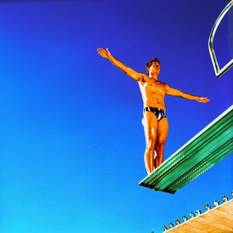 Young Man Standing on a Diving Board Backwards with Arms Outstretched