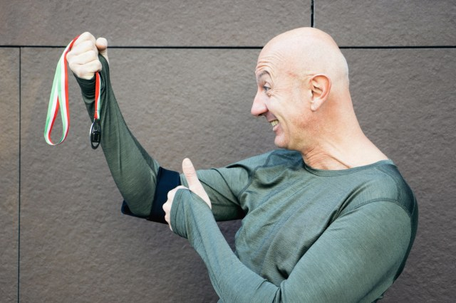 Skallet, glad mann holder opp en medalje
