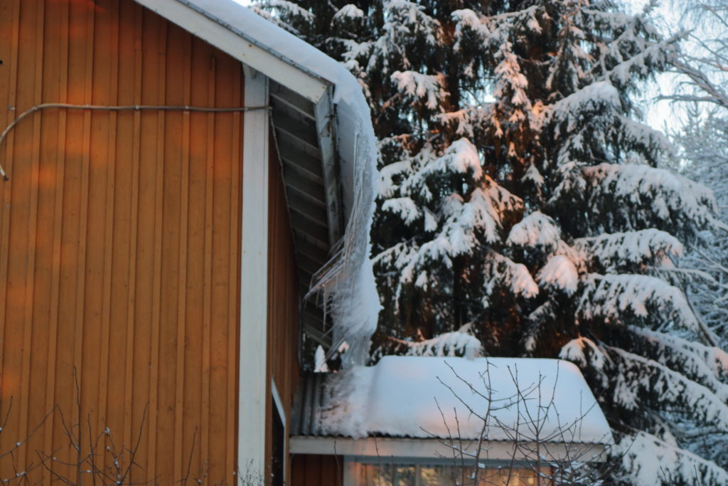 Icicles facing towards the house from the edge of its roof viewed from the side