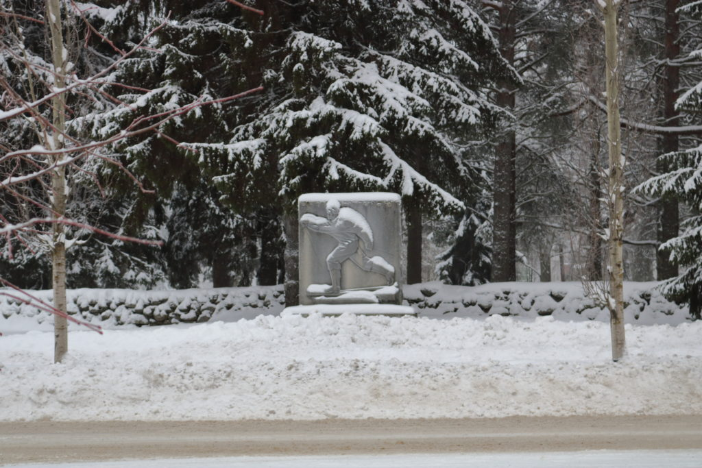 A skiing man sculpted onto stone in a snowy environment