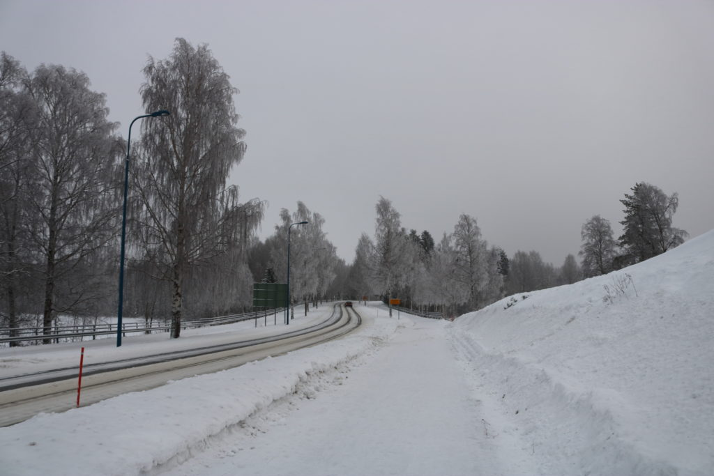 A snowy road leading away from Liperi Church