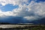 Large clouds of a storm are approaching a group of fishermen in the coursing iver