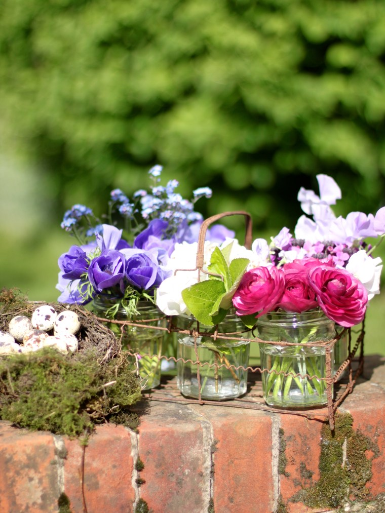 Beautiful spring flowers and a nest of birds eggs to decorate an Easter table.