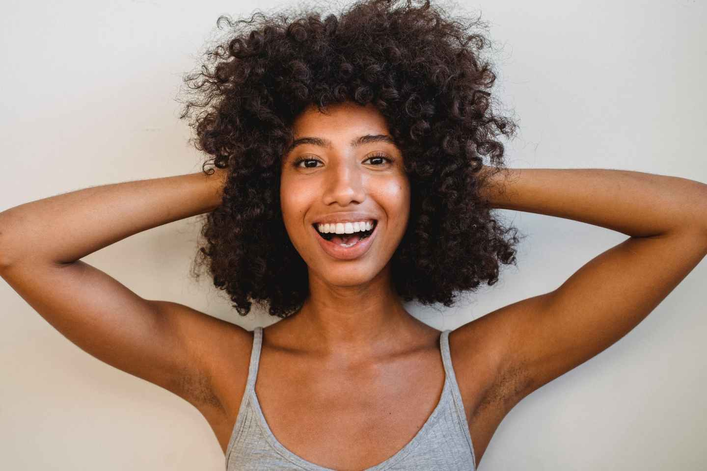 delighted black woman touching hair and looking at camera