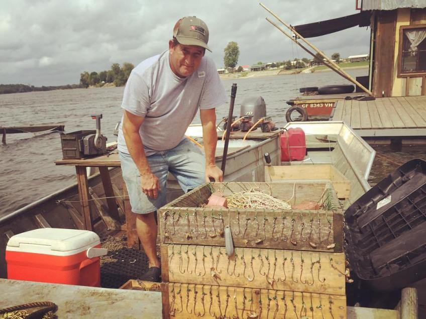 Roger Lard, fisherman near Savannah TN, trotline trays in the foreground and live catfish tank in the background