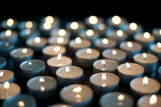 Background of burning candles of rememberance in a church, at a vigil or to celebrate a festival such as Christmas