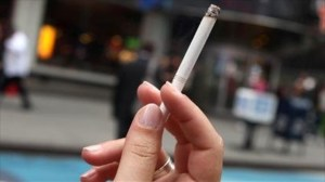 A-woman-smokes-a-cigarette-in-the-pedestrian-plaza-located-in-Times-Square-AFP