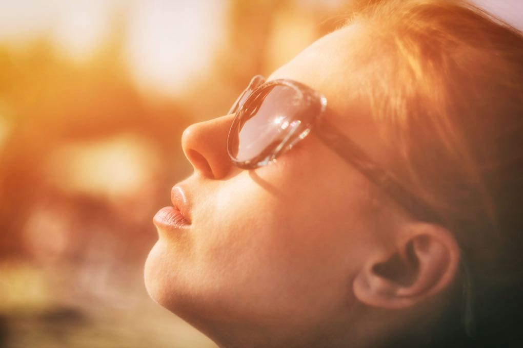 Photo of woman wearing sunglasses with face toward the sun as an example of summer skin care.