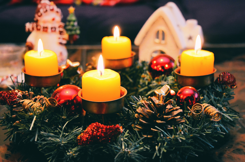 Photo of tabletop holiday wreath with burning candles as a symbol of holiday traditions