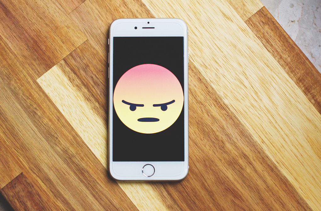 Photo of angry emoji on cellphone as example of effects of caffeine addiction