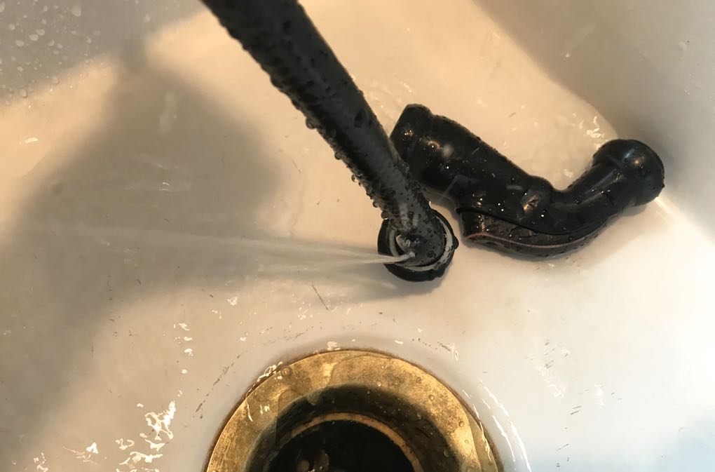 Photo of water spraying out the side of frayed kitchen sprayer hose