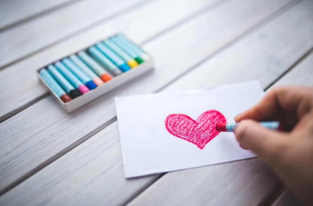 Photo of hand drawing a heart on a card as an example of Valentine's Day on a budget