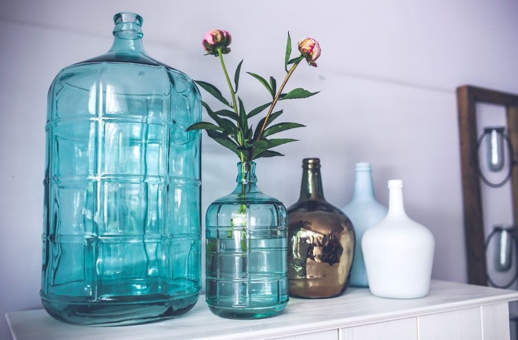Photo of large and small light green jugs and other light-colored jugs as an example of seasonal decorating