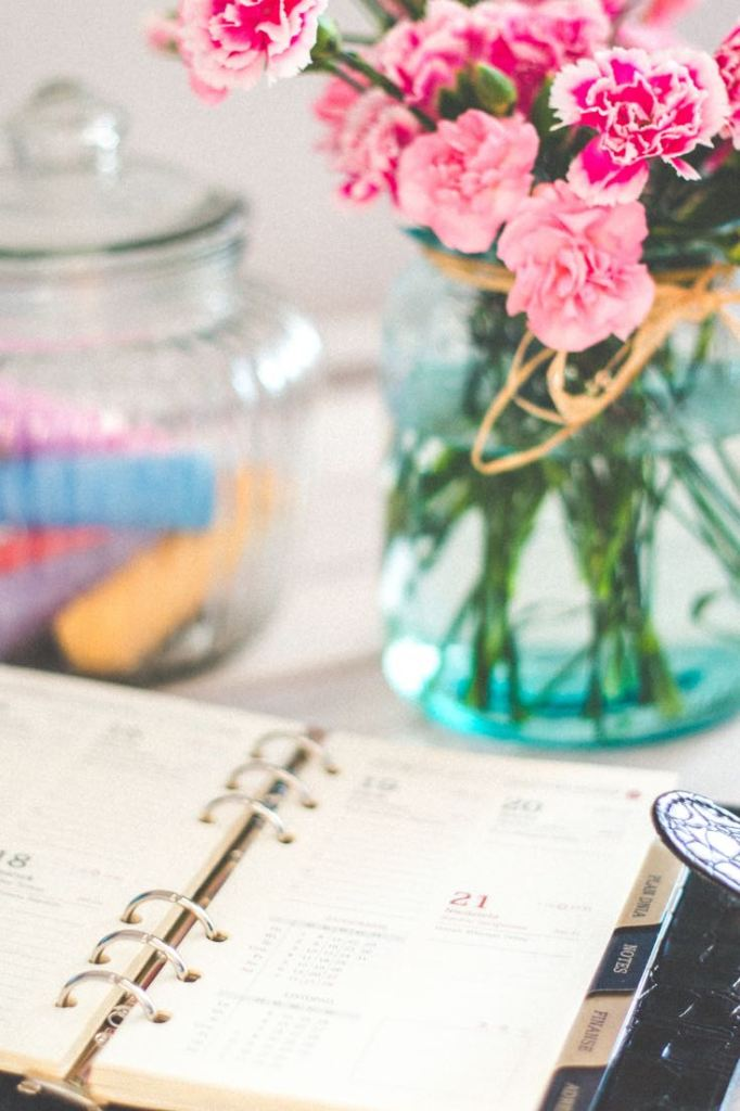 Photo of planner beside vase with pink carnations as an example of a daily schedule