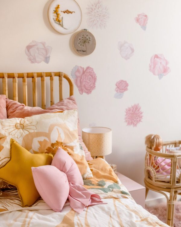Girls Bed with Vintage Style Bedlinen, Rattan Bedhead and Dolls Bassinet, Floral Wall Decals, Embroidery Hoop Wall Hangings, Cream and Mustard Bedside Lamp and Medium Mustard Star and Rose Pink Bow Cushions