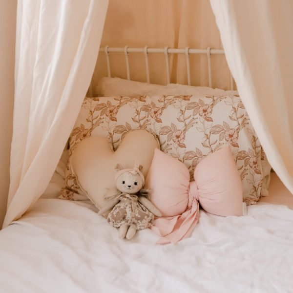 Girls Bed - Beige Canopy, Vintage Floral Bedlinen, Small Soft Toy and Medium Natural Heart and Baby Pink Bow Cushions sitting on bed