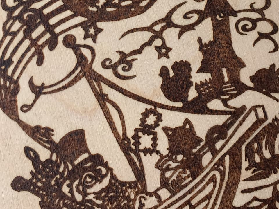 closeup photo of the 'owl and the pussycat' pyrography design we created for our wedding stationery