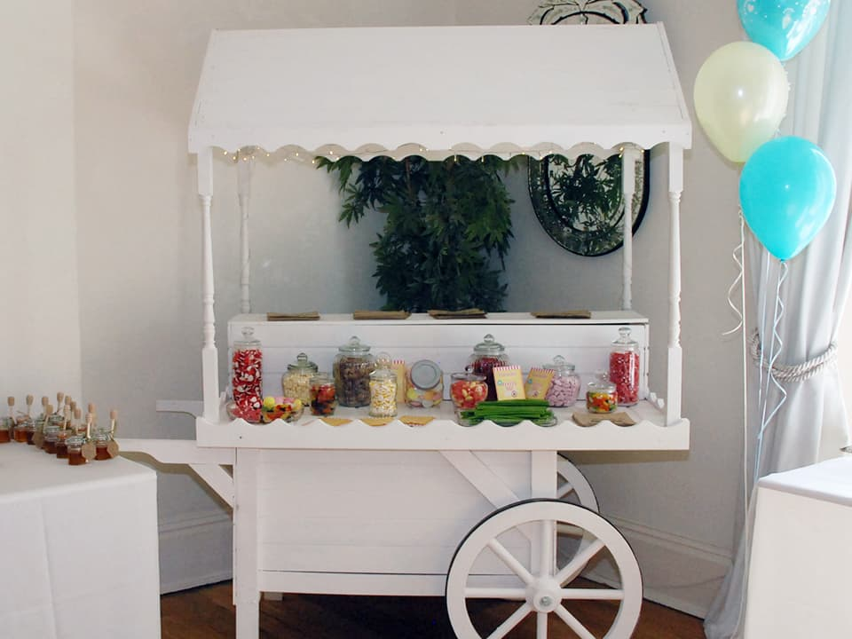White painted sweet cart or 'candy cart' at our wedding decorated with lights and lots of sweets
