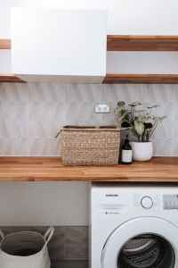 washing machine under wooden table with plant and wicker basket