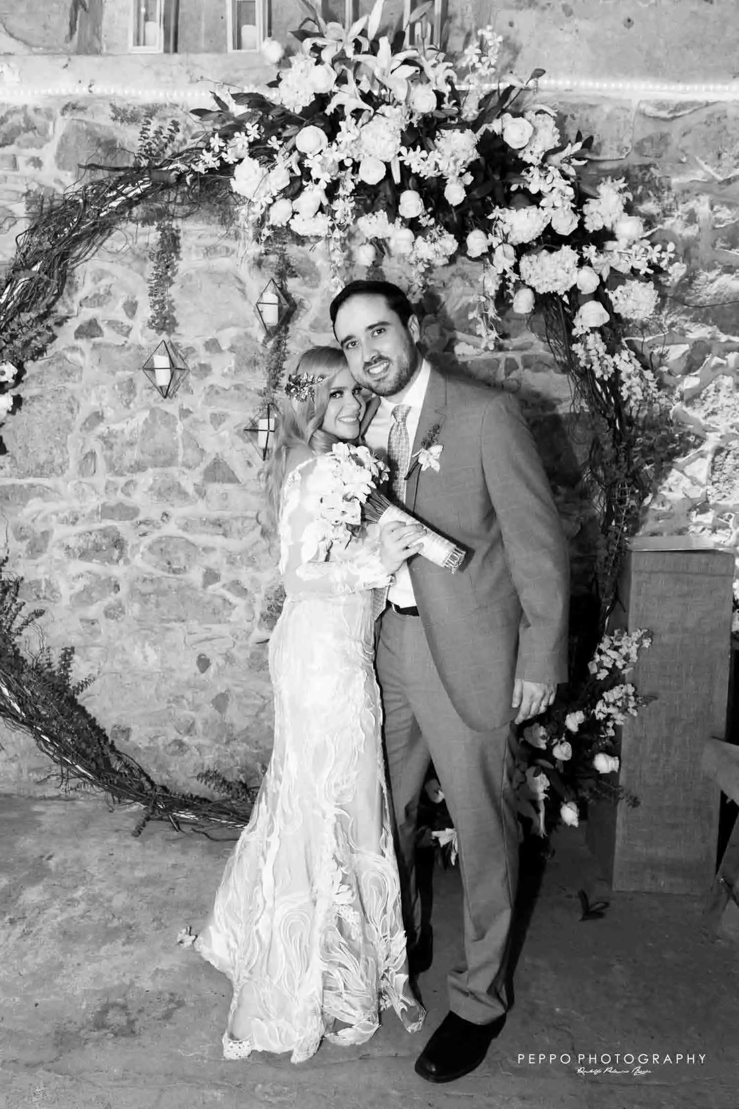 Los nuevos esposos posando en el arco de flores