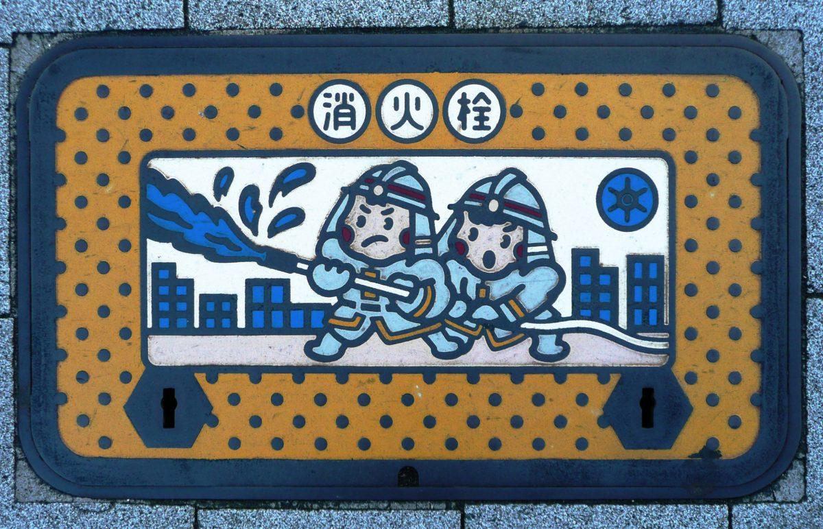 Plaque d'incendie rectangulaire sur laquelle deux pompiers tiennent une lance à incendie - vue à Tokyo