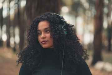 content ethnic woman with headphones in park