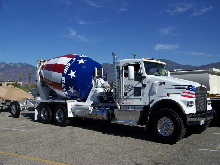 A concrete mixer with the flag of America posted on it.