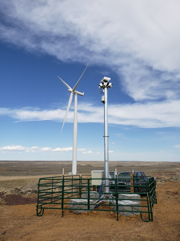 A close up photo of the IdentiFlight automated curtailment system in front of a wind turbine