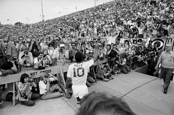 New York Cosmos' Pele flashes a v sign to the crowd before making his NASL debut